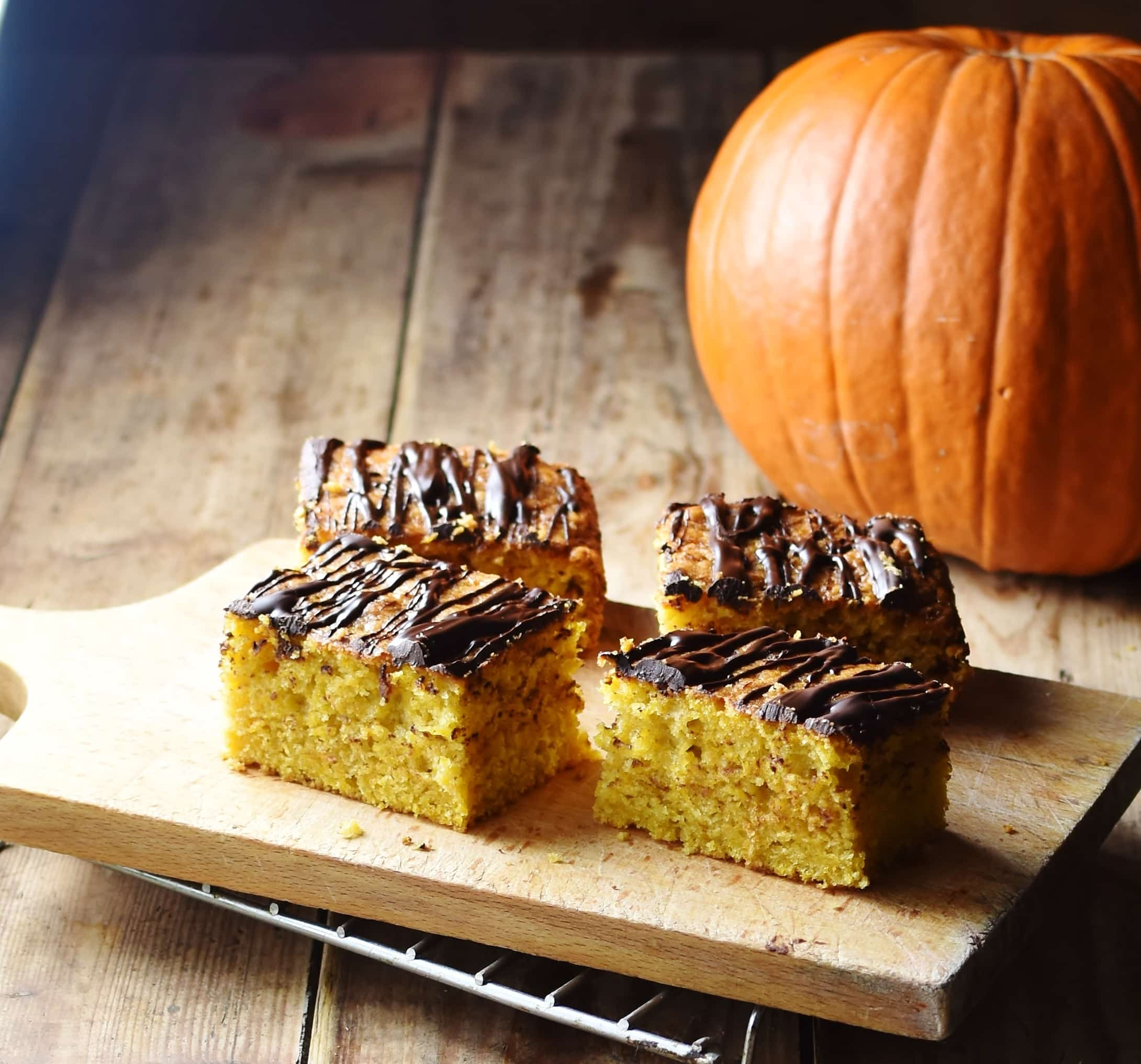 4 slices of pumpkin cake with chocolate drizzle on top of cutting board, with pumpkin in background.