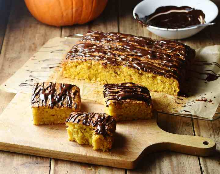 Side view of healthy pumpkin cake slices on top of cutting board, with cake, pumpkin and melted chocolate in white bowl in background.