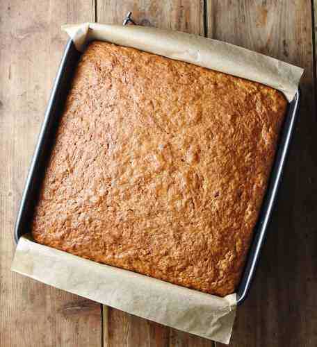 Baked healthy pumpkin cake in square pan with parchment paper visible.