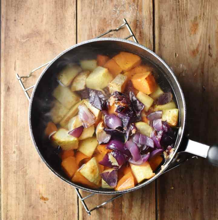 Chunks of root vegetables and chopped red onion in large pot with water.