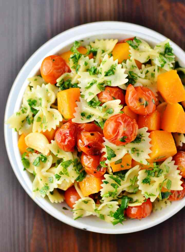 Top down view of pasta with butternut squash pieces, cherry tomatoes and herbs in white bowl on top of white plate.