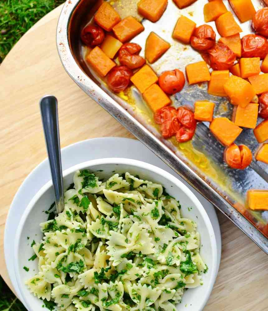 Top down view of pasta with herbs and spoon in white bowl on top of white plate, and roasted butternut squash chunks with cherry tomatoes in roasting tin.