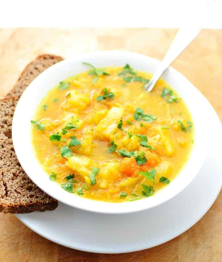 Root vegetable soup in white bowl with spoon on top of white plate with dark bread slices to left.