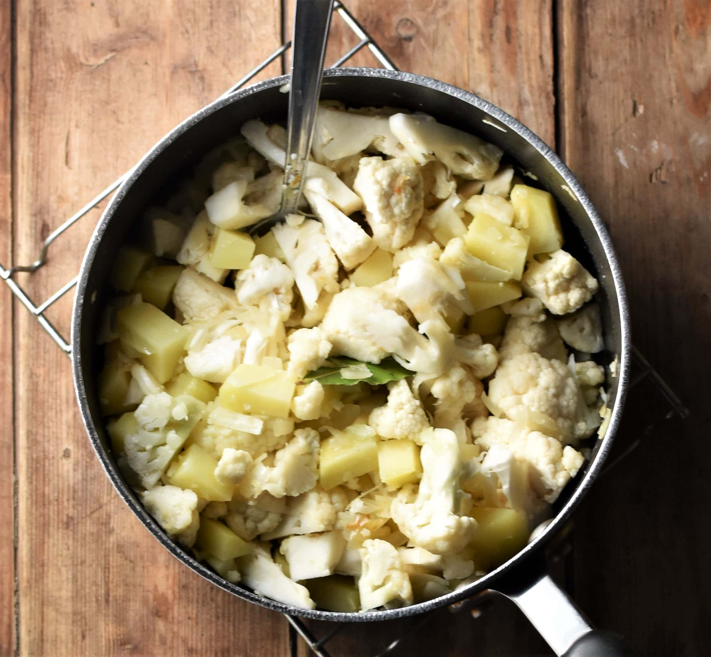 Cauliflower pieces and cubed potatoes in large pot with spoon.