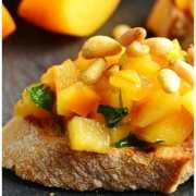 Chopped persimmon with pine nuts on top of bread slice, with persimmon wedges in background.