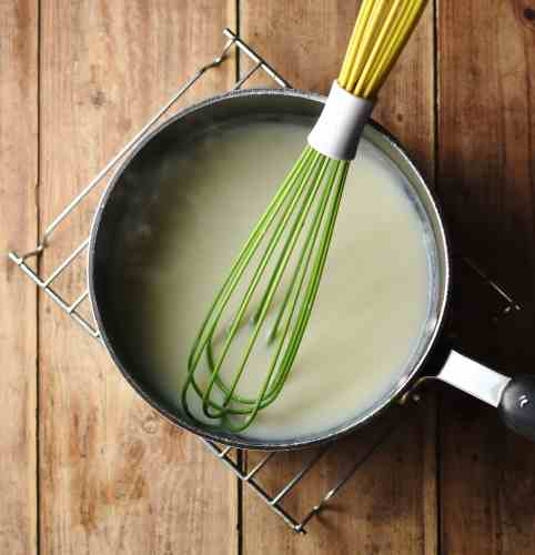 White sauce in large pot with green whisk on top of cooling rack.