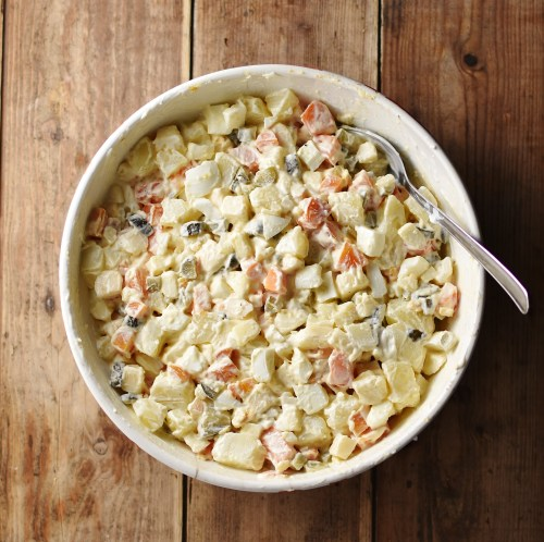 Top down view of potato salad with spoon inside large white bowl.