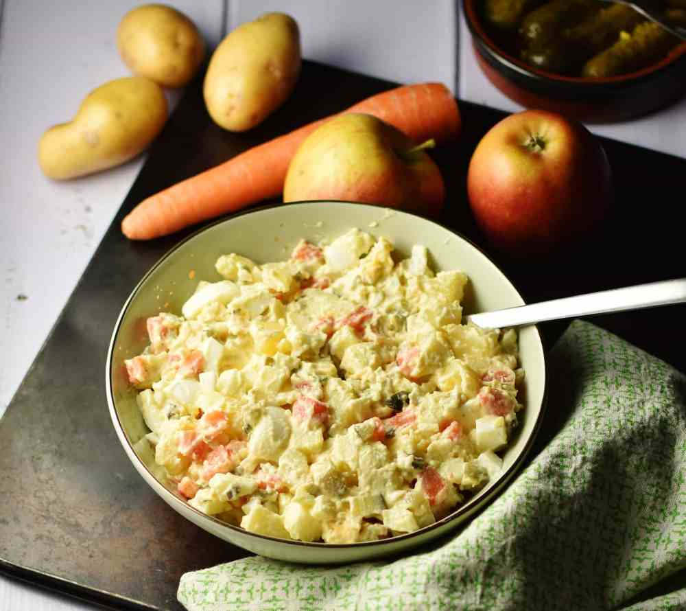 Potato salad with spoon in green bowl on top of oven tray, with green cloth in bottom right corner and raw carrot, apples and potatoes in background.