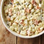 Top down partial view of potato salad in white bowl.