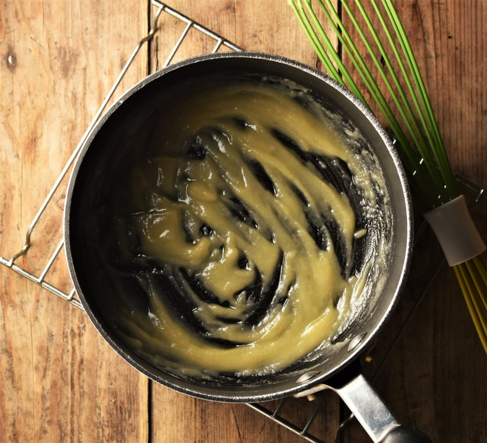 Thick paste (roux) in black saucepan on cooling rack with green whisk in background.
