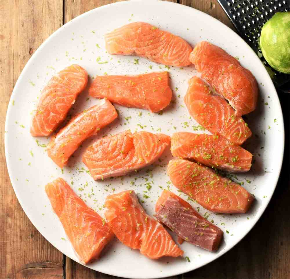 Raw salmon pieces with lime zest on top of white plate.