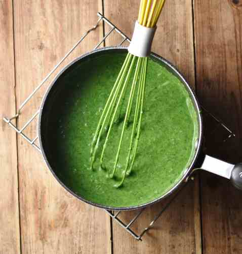 Top down view of spinach sauce inside large pot with green whisk.