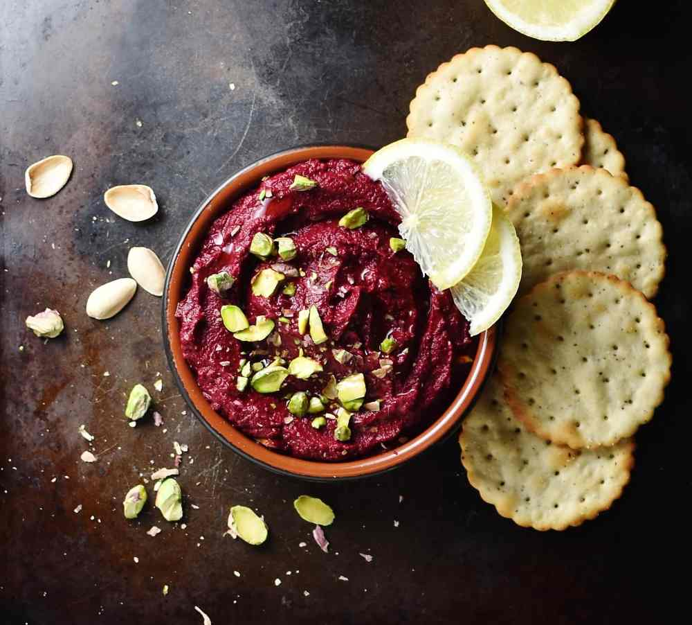 Beet dip with chopped pistachios and lemon wedges inside brown dish, with crackers and pistachios scattered around.