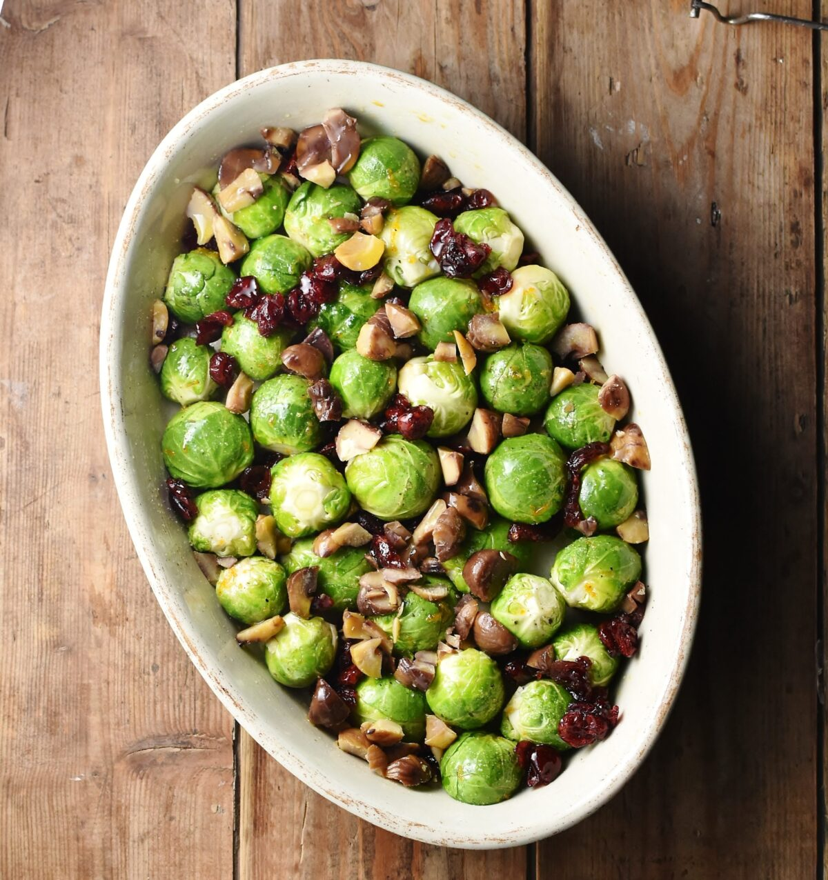 Brussels sprouts with dried cranberries and chestnuts in white oval dish.