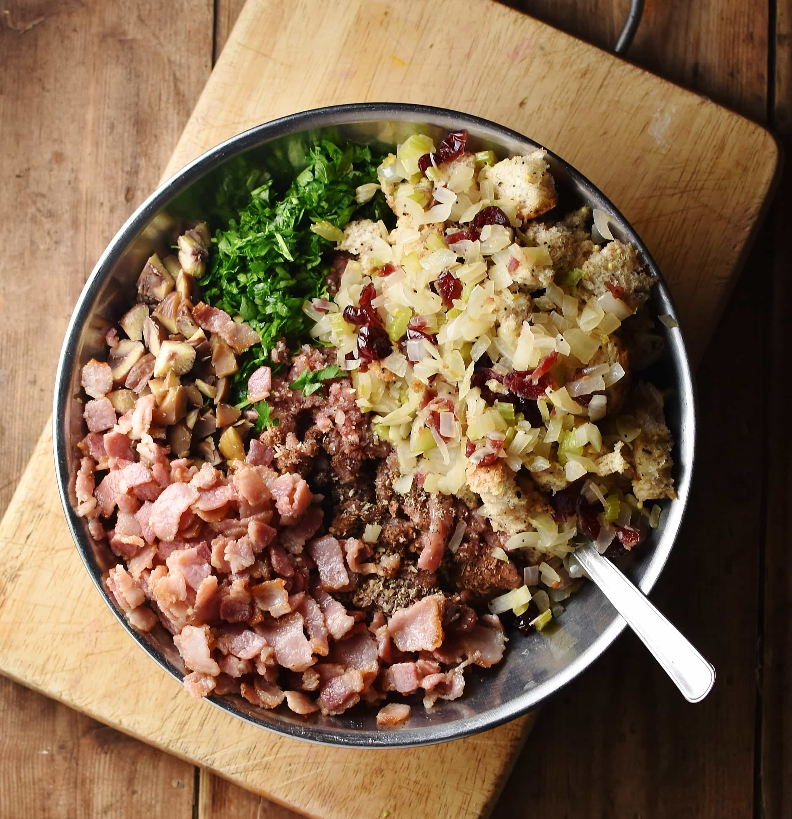 Bacon pieces, herbs, ground turkey, cranberries, chestnuts and chopped onions in large metal bowl with spoon on top of wooden board.
