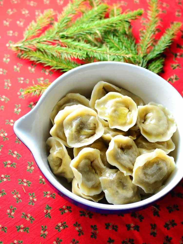 Polish Christmas Eve porcini dumplings (uszka) in white bowl with pine tree branch on red cloth with hollies pattern.