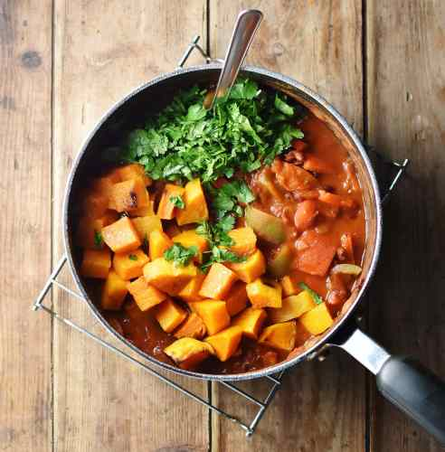 Cubed squash, herbs and tomato sauce in large pot with spoon.