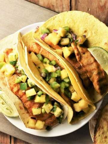 3 tortillas with chicken and pineapple salsa on plate.