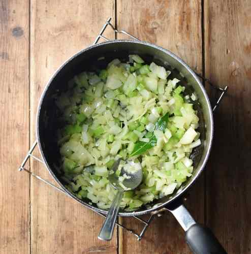 Chopped onions and celery in large pot with spoon.
