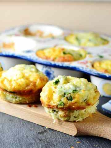 Asparagus egg muffins on wooden board with ceramic muffin tin in background.