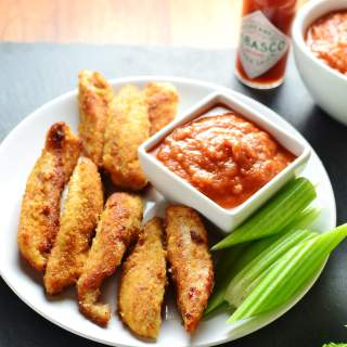 Fried breaded chicken tenders with Bloody Mary dip in white square dish and celery sticks on white plate and tabasco sauce in background.