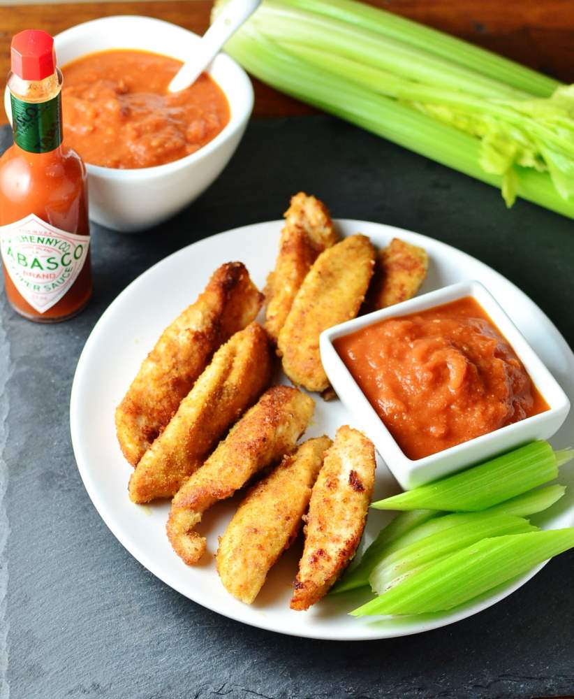 Homemade fried breaded chicken tenders with Bloody Mary dip in white square dish and celery sticks on white plate and tabasco sauce, celery and dip in white bowl with spoon in background.