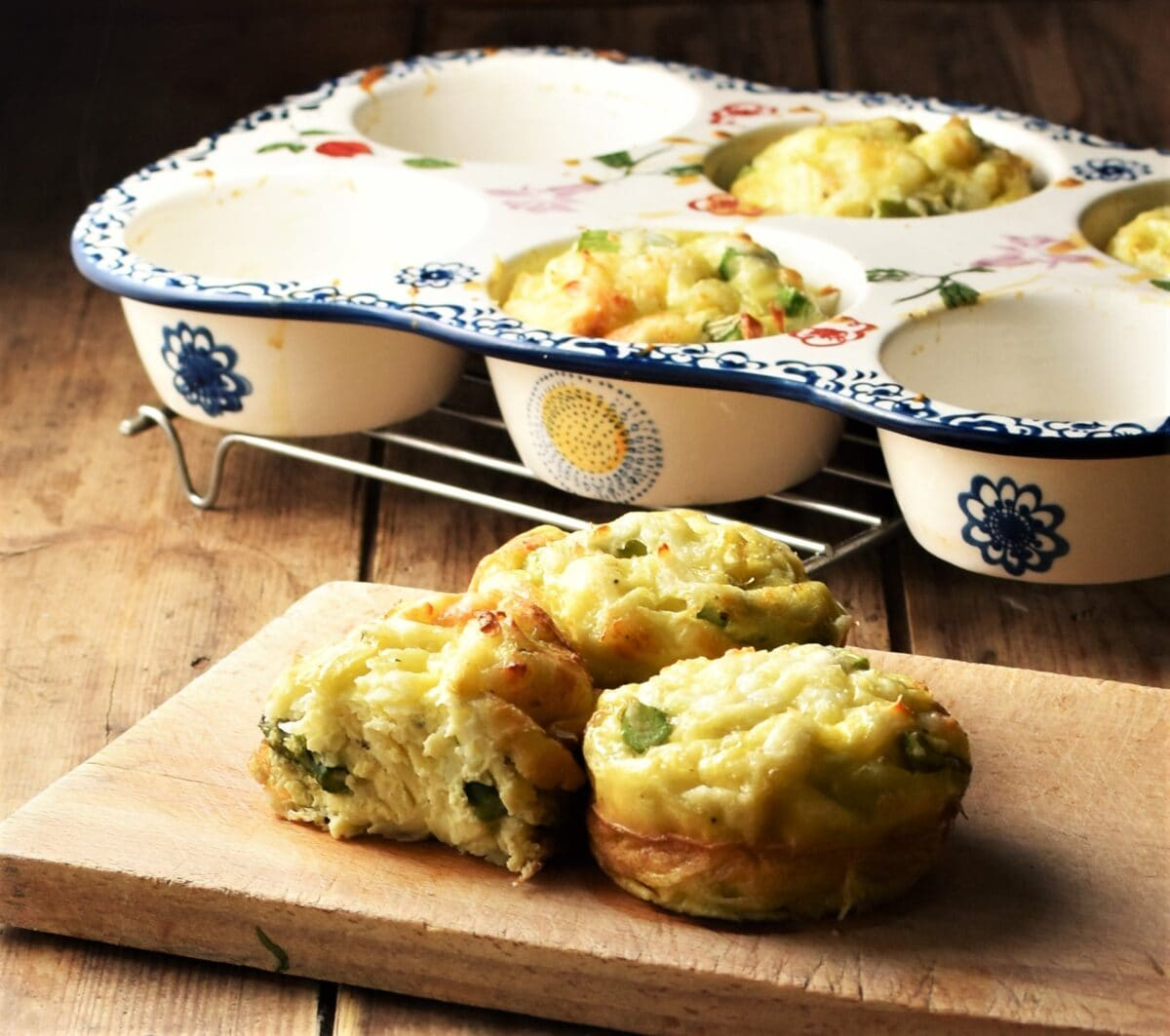 Side view of egg asparagus muffins on top of wooden board, with white ceramic muffin pan with blue flowery pattern in background.