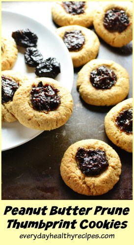 Peanut butter thumbprint cookies on white plate and metal background.