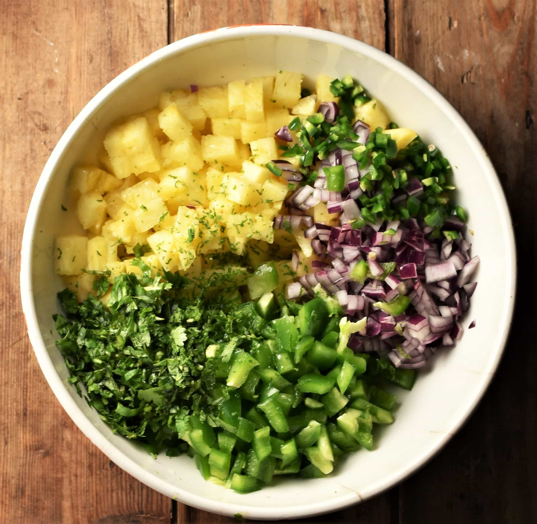 Chopped pineapple, green pepper, cilantro and red onion in white bowl.
