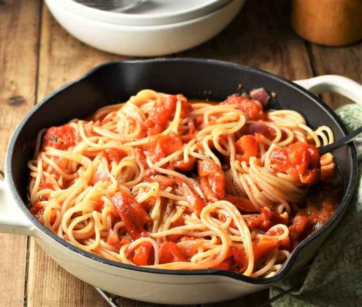 Side view of red pepper spaghetti in pan with fork.