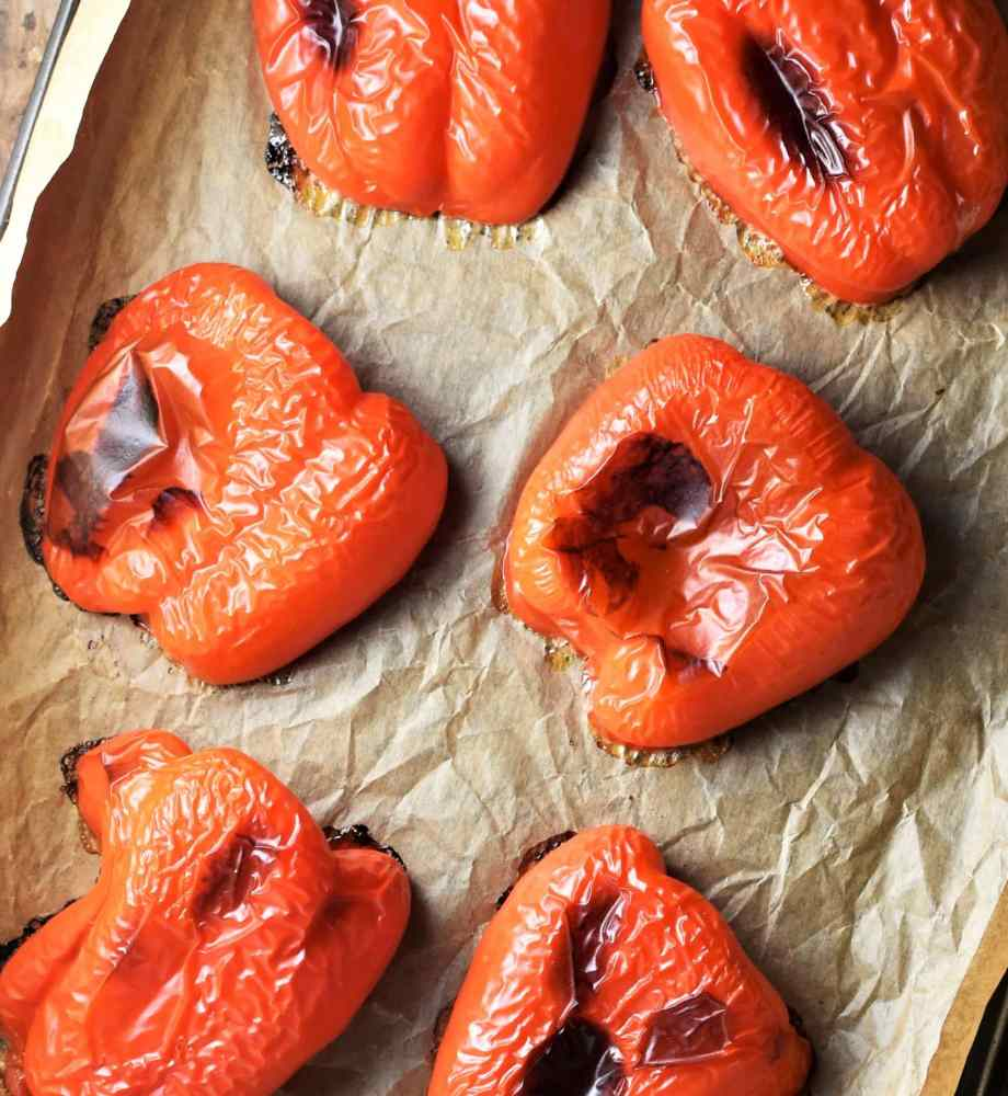 Roasted red bell pepper halves on top of parchment.