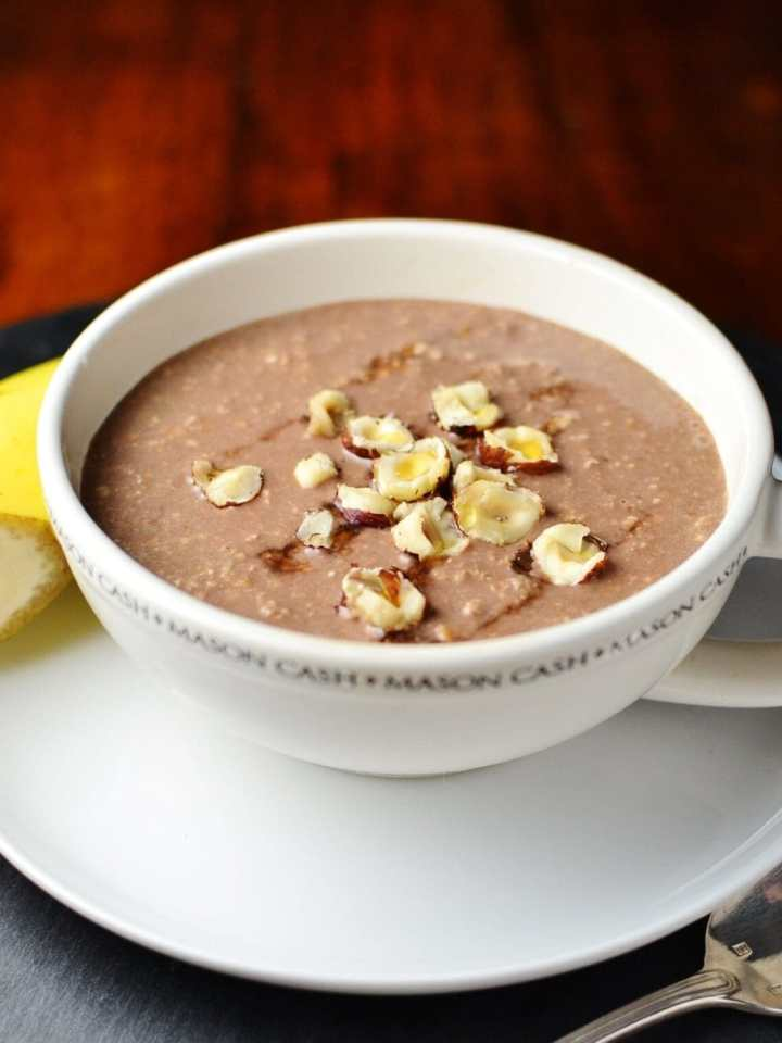 Mocha overnight oats topped with crushed hazelnuts in coffee cup on top of saucer with half banana in background.