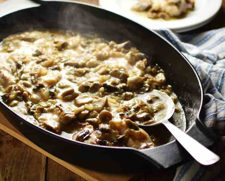 Side view of chicken mushroom casserole in black oval dish with spoon.
