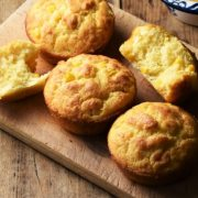 Cornmeal muffins on top of wooden board with milk in background.