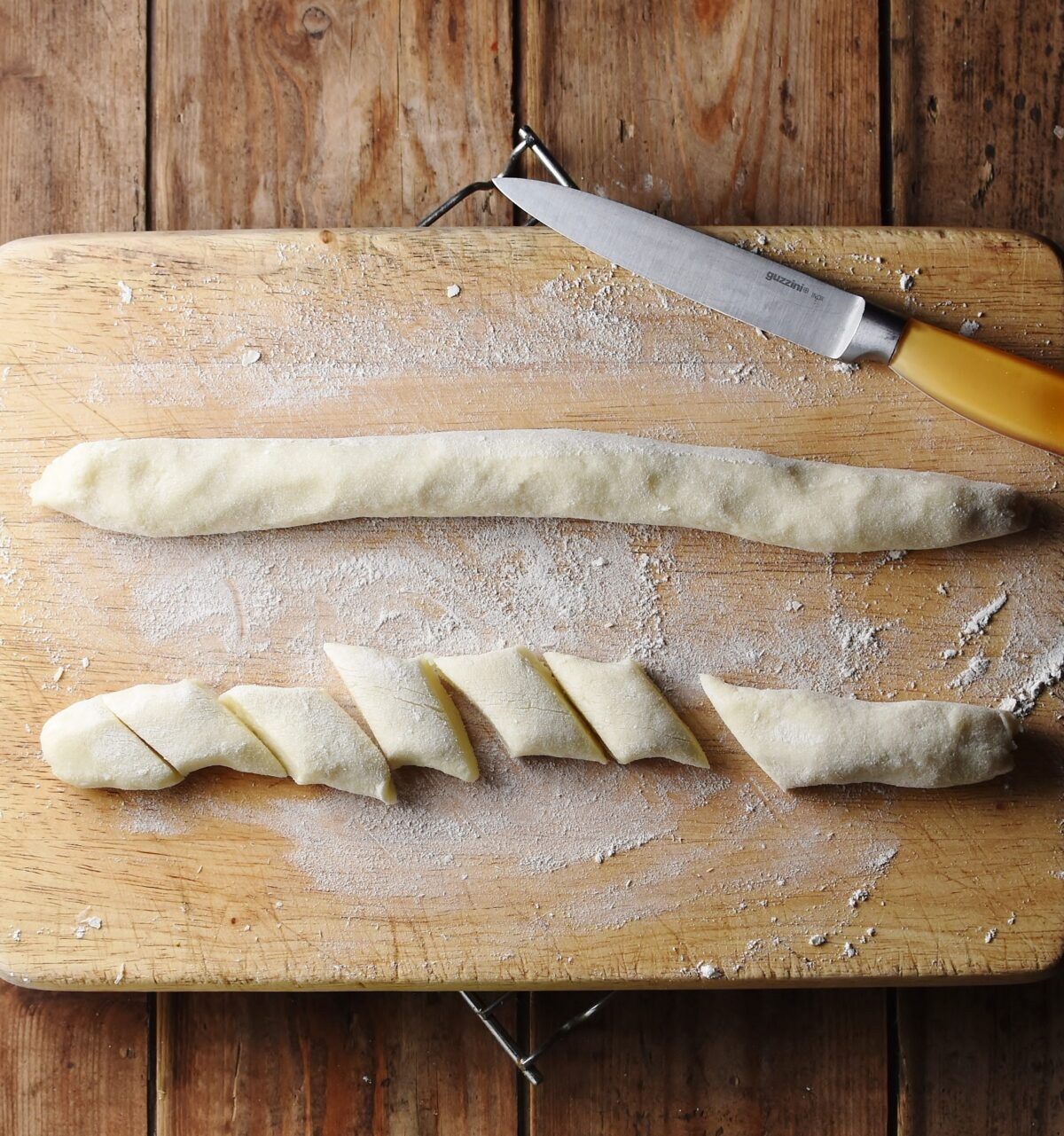2 sausage shaped dough parts, one of them cut into pieces, on top of floured wooden board with small yellow knife.