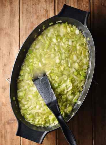 Leek stew with black spatula in black, oval shallow dish.