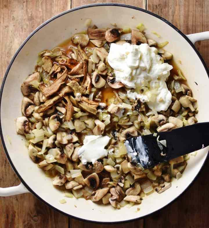 Chunky mushrooms with yogurt and black spatula inside white shallow pan.