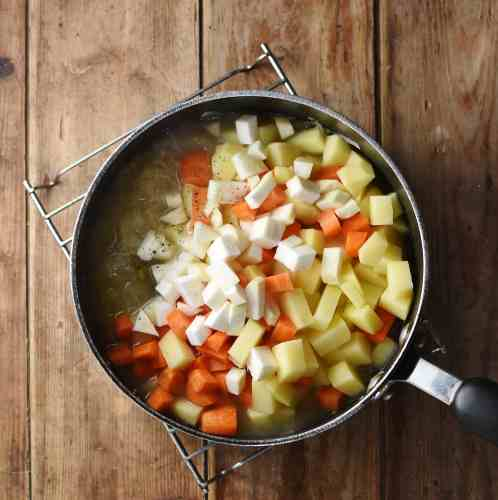 Cubed carrots, potatoes and celeriac in large pot.