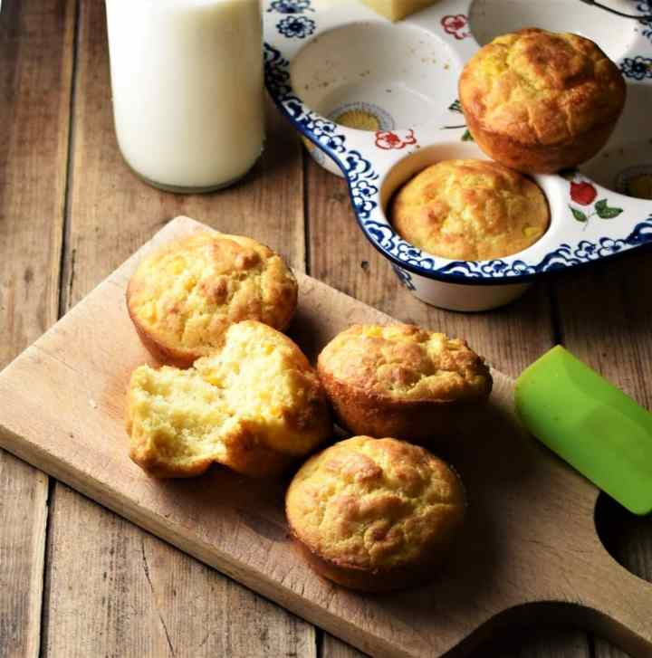 Cornbread muffins on top of wooden board, with milk in bottle, muffins in white ceramic pan with blue flowery pattern and green spatula in background.
