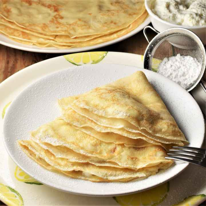 Side view of cheese crepes on plate with powdered sugar and crepes in background.