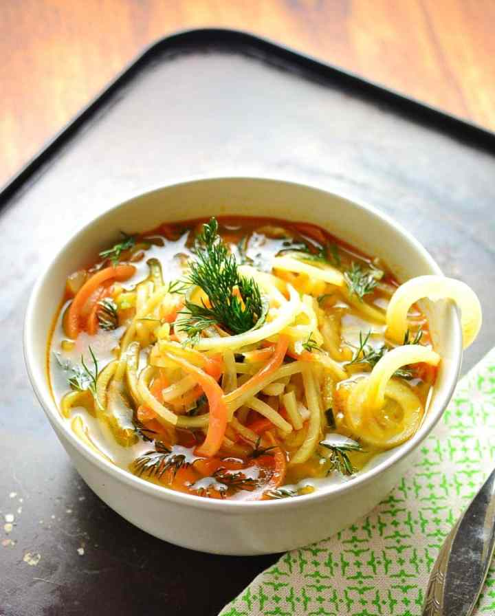 Spiralized vegetable soup in white bowl with green cloth on oven tray.