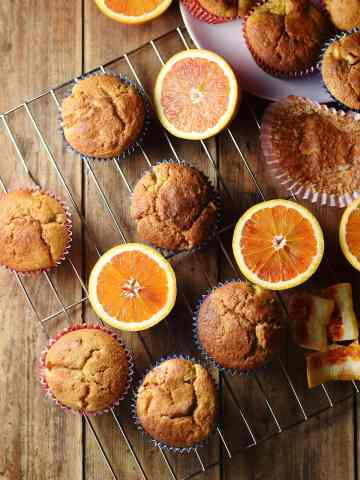 Top down view of muffins and halved blood oranges on rack.