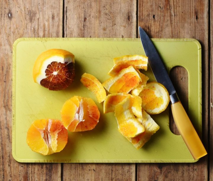 Peel and cut blood oranges and yellow knife on top of yellow board.