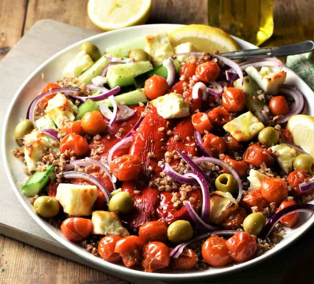 Buckwheat salad with roasted vegetables and feta on large plate.