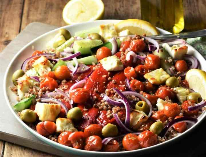 Side view of buckwheat salad with roasted vegetables, olives and feta on white plate.