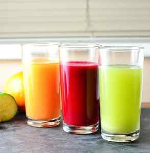 Cabbage juice in three glasses, green, red and orange, with fruit and vegetables in background on slate surface.