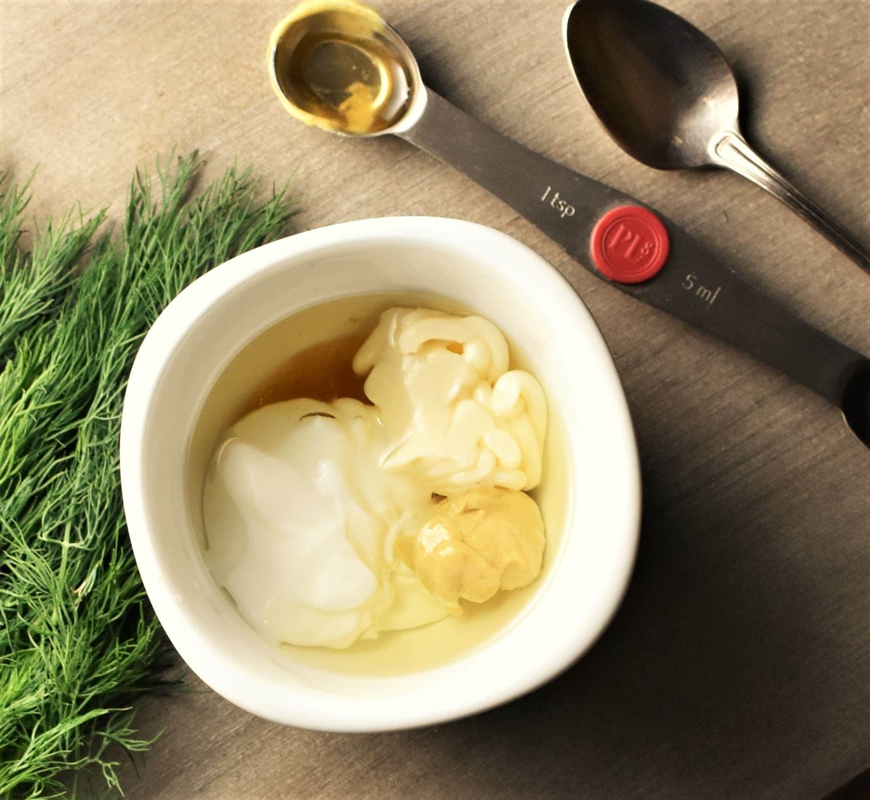 Yogurt and mustard dressing ingredients in white dish, with dill and spoons in background.