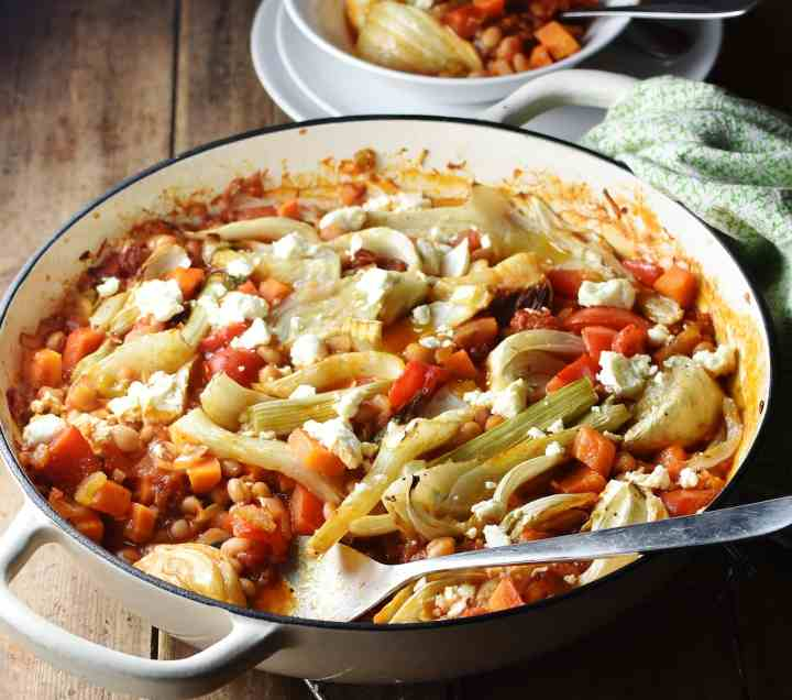 Side view of vegetable casserole with fennel pieces and beans in large shallow white dish with spoon, and white plates and casserole in bowl in background.