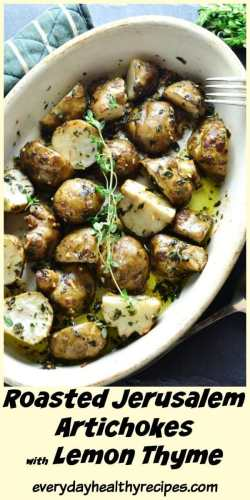 Close-up view of roasted Jerusalem artichokes with thyme sprigs in white oval dish.
