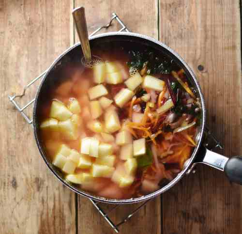 Vegetables and cubed potatoes with spoon inside soup in large pot.